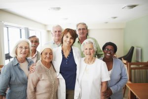 A smiling female doctor surrounded by a group of her elderly patients